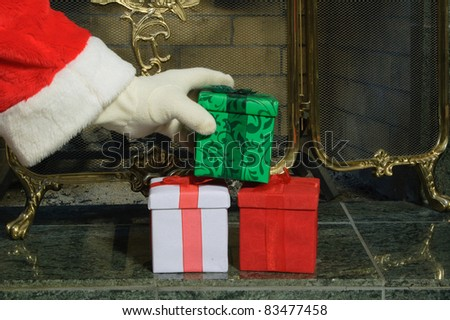 closeup of Santa's gloved hand placing gifts by the fireplace on the hearth - stock photo