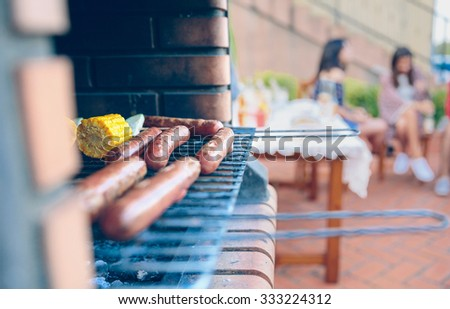Closeup of sausages and corn cobs cooked in a brick barbecue with group of friends sitting talking on background in a outdoors summer party - stock photo