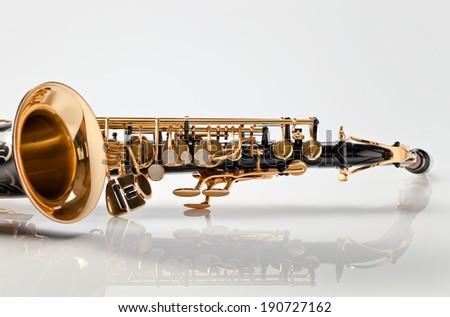 closeup of saxophone on white reflexive background - stock photo