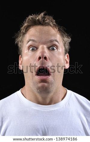 Closeup of scared Caucasian man with eyes and mouth wide open in fear on black background