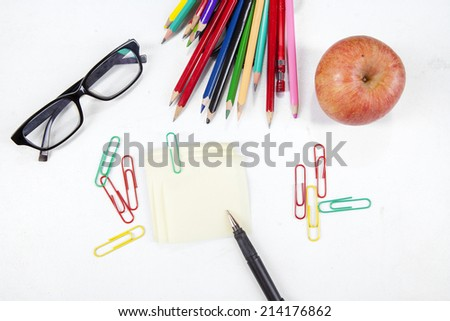 Closeup of school stationery and red apple, symbolizing back to school - stock photo
