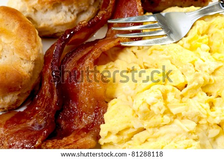 Closeup of scrambled eggs, bacon slices, biscuits, and fork - stock photo