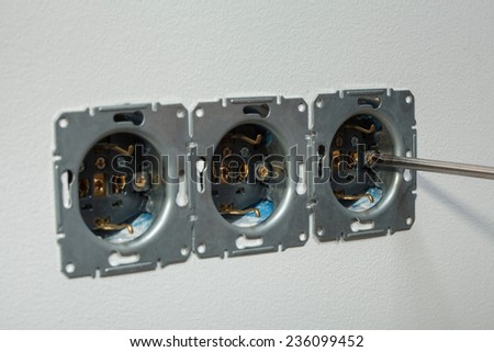 Closeup of screwing screws with a hand screwdriver, mount wall socket. - stock photo