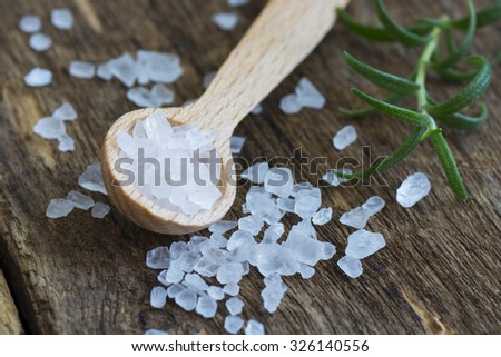 Closeup of sea salt on wooden table - stock photo