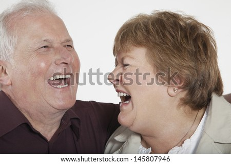 Closeup of senior couple laughing on white background