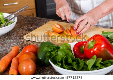 closeup of senior female chopping food ingredients in the kitchen - stock photo