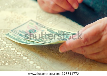 Closeup of senior lady with dollar bills in hands, toned image instagram-like color, selective focus, very shallow DOF. Hand holding money american dollars on colorful background - stock photo