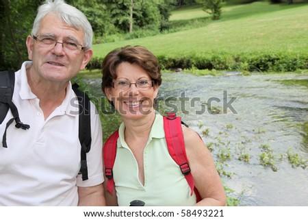 Closeup of senior people rambling by a river - stock photo