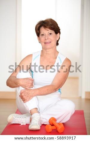 Closeup of senior woman doing stretching exercises - stock photo