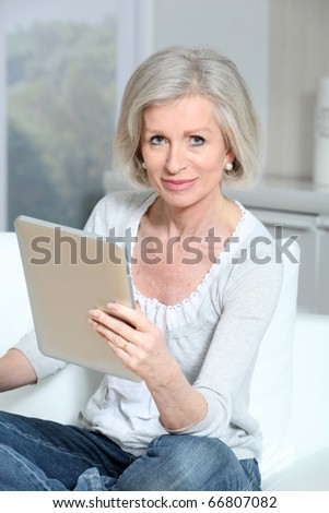 Closeup of senior woman sitting on sofa with electronic pad - stock photo