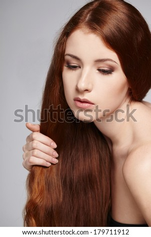 Closeup of sensual beautiful redheaded woman, over gray background