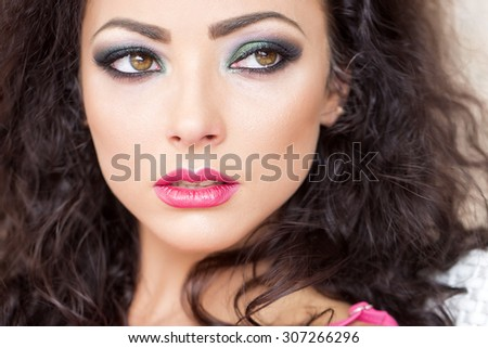 Closeup of sensual pretty young brunette girl with curly hair bright makeup expressive green brown eyes and pink lips looking away sitting outdoor, horizontal picture - stock photo