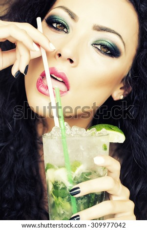 Closeup of sensual young brunette woman with curly hair and bright makeup drinking alcoholic mojito cocktail from mint soda light rum ice cubes and lime with straw, vertical picture - stock photo