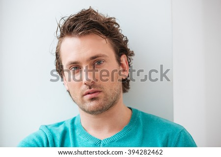 Closeup of serious attractive young man with curly hair over white background  - stock photo