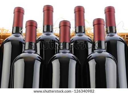 Closeup of seven Cabernet Sauvignon Wine Bottles in Crate with Straw on a white background. - stock photo