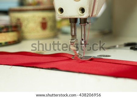 Closeup of sewing machine needle stitching red colored cloth to satin ribbon - stock photo