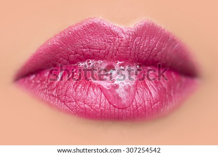 Closeup of sexual closed female mouth of beautiful young woman with foam beverage bubbles on bright pink lips on tan beige face, horizontal picture - stock photo