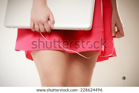 Closeup of sexy female legs and white computer laptop with headphones on gray. Girl listening to music. - stock photo