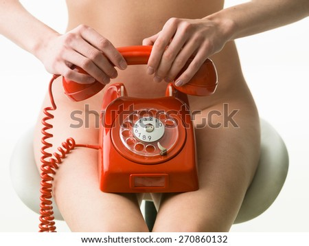 closeup of sexy naked woman sitting on chair and holding red vintage phone - stock photo