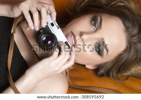 Closeup of sexy young model woman with bright makeup in black dress without shoulder-straps looking forward lying on leather brown royal sofa holding photographic camera, horizontal picture