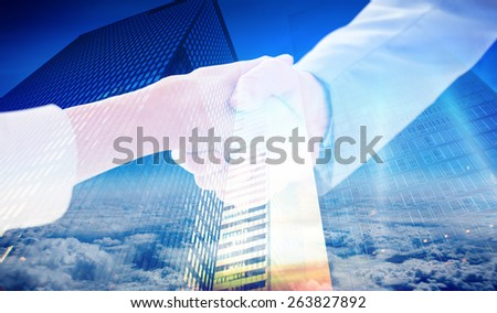 Closeup of shaking hands after business meeting against low angle view of skyscrapers at sunset - stock photo