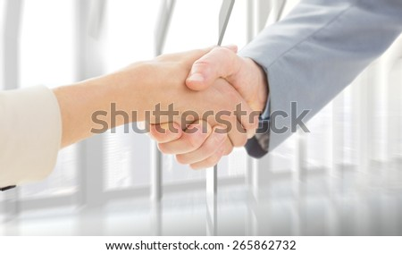 Closeup of shaking hands after business meeting against room with large window looking on city - stock photo