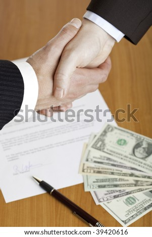Closeup of shaking hands with contract, money and pen in background. - stock photo