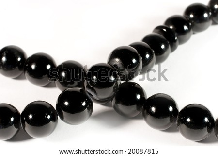 Closeup of shiny black beads (on white)