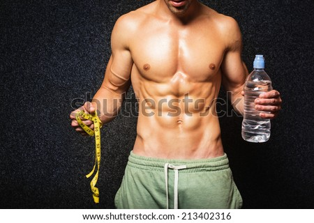 Closeup of shirtless fitness guy holding bottle of water and tape measure. Torso and abdominal muscles of muscular slim young man. Healthy lifestyle concept. - stock photo