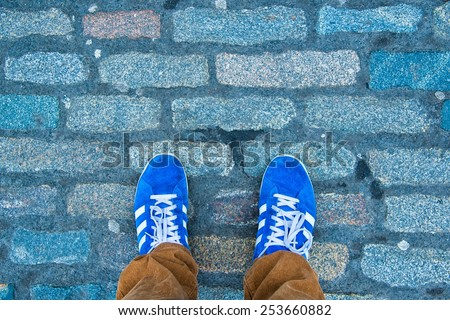 Closeup of shoes on old rocks path - stock photo