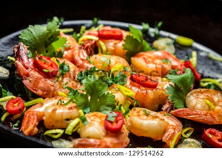 Closeup of shrimps on pan with herbs - stock photo