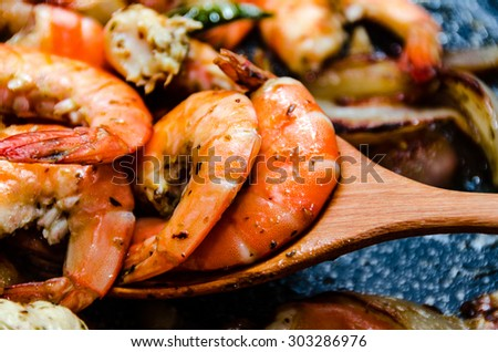 Closeup of shrimps on pan with herbs