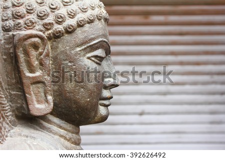 Closeup of side view of Gautaum Buddha statue in front of closed shutter  - stock photo