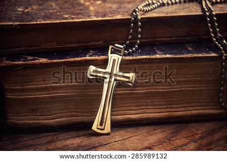 Closeup of silver Christian cross on bible - stock photo