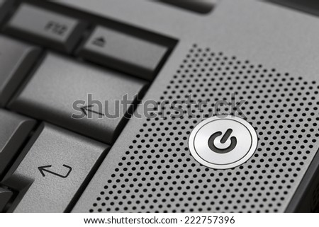Closeup of silver computer laptop selective focus on standby on button ideal for technology business start power energy symbol. - stock photo