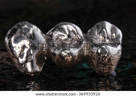 Closeup of silver/metal cast molars-crowns on black background - stock photo