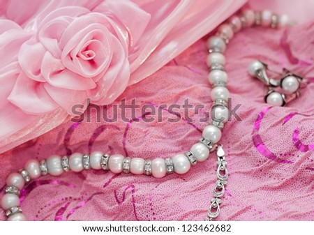 Closeup of silver pearl jewellery on the a pink dress - stock photo