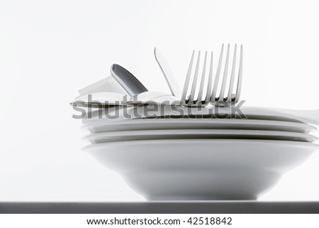 closeup of silverware on pile of plates with white cloth - stock photo