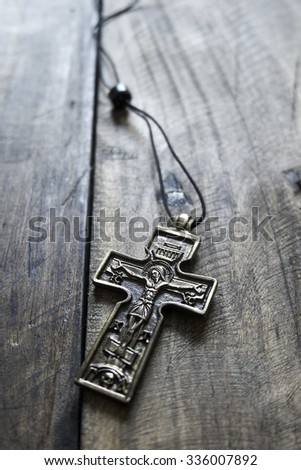 Closeup of simple  Christian cross necklace on wooden background - stock photo