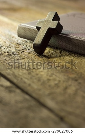 Closeup of simple wooden Christian cross necklace on holy Bible