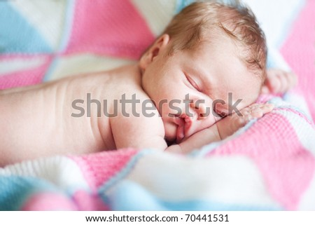 Closeup of sleeping baby lying on blanket with hands in a comfortable position