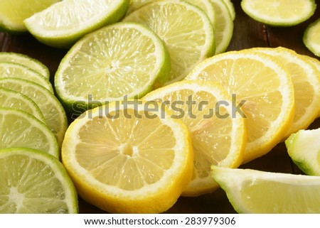 Closeup of slices and wedges of lemons and limes - stock photo