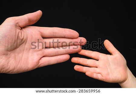 Closeup of small and big caucasian hand palms touching isolated towards black background