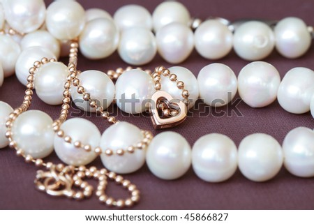 Closeup of small gold heart and pearl necklace on textiles background