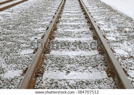 Closeup of small white ice crystals forming on railway train tracks during winter