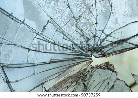 Closeup of smashed glass panel cracked and broken - stock photo