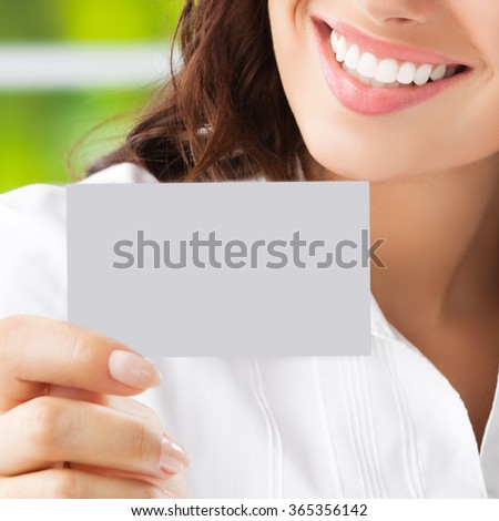 Closeup of smiling businesswoman showing blank business or plastic card with copyspace area for slogan or text. Invitation concept. - stock photo