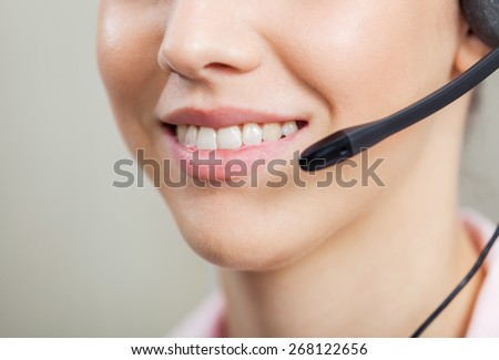 Closeup of smiling female customer service representative wearing headset in office - stock photo