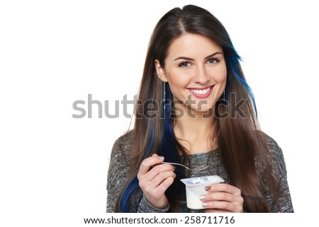 Closeup of smiling healthy woman eating yoghurt isolated on white - stock photo