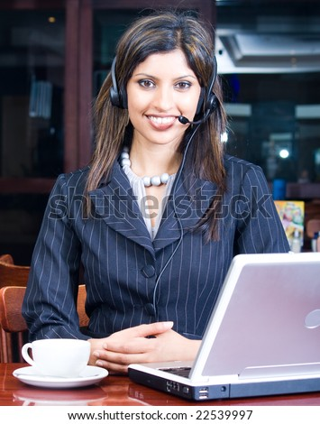 closeup of smiling indian business woman with headset and laptop in a cafe - stock photo